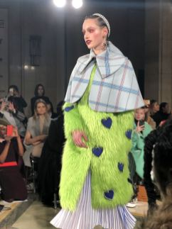 A model on the runway for STARSICA FW18 LONDON FASHION WEEK wearing fuzzy green faux fur and a checked cape