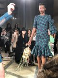 STARSICA FW18 LONDON FASHION WEEK a model wearing a checked dress and carrying a birdcage