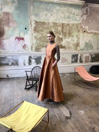 Merchant Archive FW18 LFW a model wears one of the standout looks from the collection. A russet coloured dress with full skirt layered over a long sleeved tee