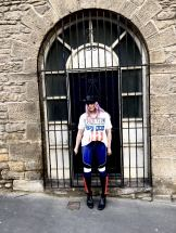 Pixie tenenbaum wearing the GIGI x TOMMY leather speed motocross style pants with a Led Zepplin tee and a baker boy hat in front of a wrought iron gate in Newcastle