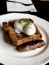 two perfectly poached eggs on wholemeal toast with a sausage on the side at Forsyth & Reed