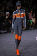 An image from the SS18 Fenty puma runway show, a model in a neoprene motocross inspired jumpsuit