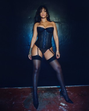 Rihanna wears a black basque, panties and suspenders in a full length campaign shot from her debut lingerie line Savage x Fenty