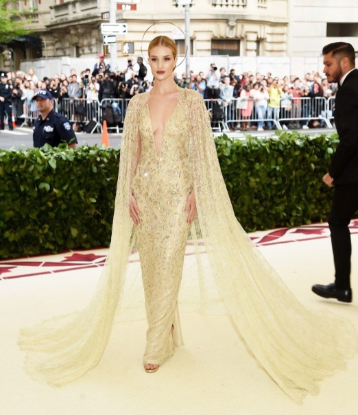 rosie Huntington Whiteley in a gold plunge neck gown with gold cape and halo on the red carpet of the 2018 met gala