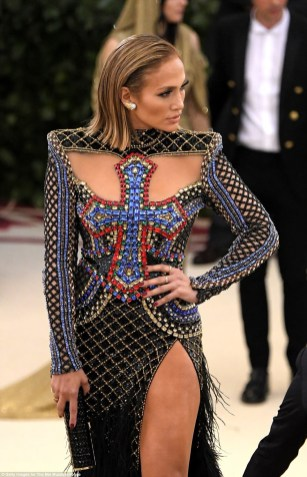Jennifer lopez on the steps to the met gala wearing a bejewelled split front dress emblazoned with cross detailing