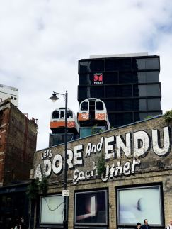 Street Art in Shoreditch: Adore and Endure painted on a wall with two real tube trains above it