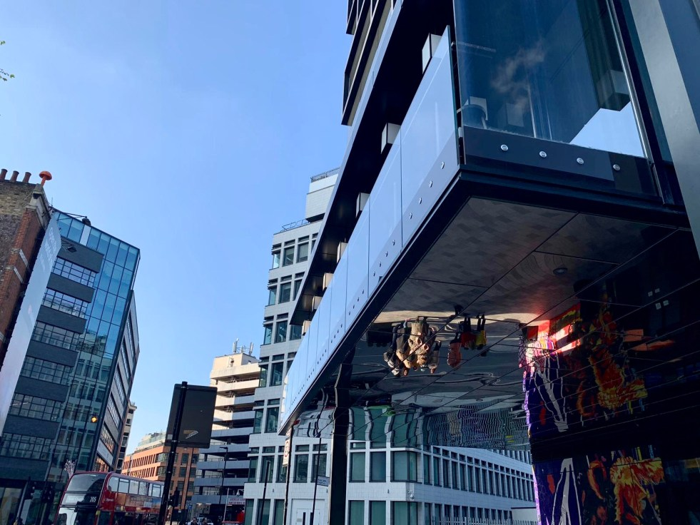 iPhone XS Camera Trial: An image showing depth of perception and perception of depth. A mirrored office block reflects the buildings around it, some have street art painted on to them, there are trees close in the foreground and towerblocks in the distance demonstrating the camera's ability to photograph depth and translate this into an image. Fashion Voyeur Blog