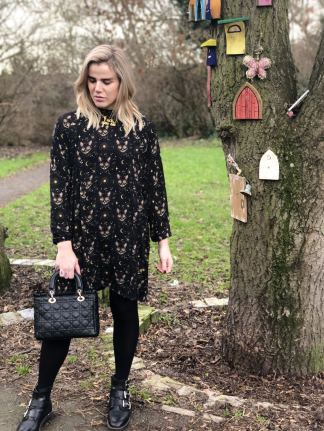 An image of Blogger Pixie Tenenbaum in a park next to a tree decorated with fairy doors. She is wearing a long sleeved cat print midi dress and buckled boots and holding a Lady Dior bag. she is looking towards the ground on the day of her 40th birthday ready to go out to dinner