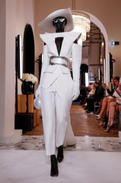 An image of a runway model at the Balmain couture Spring 2019 show wearing a white geometric angled suit with pointed shoulders