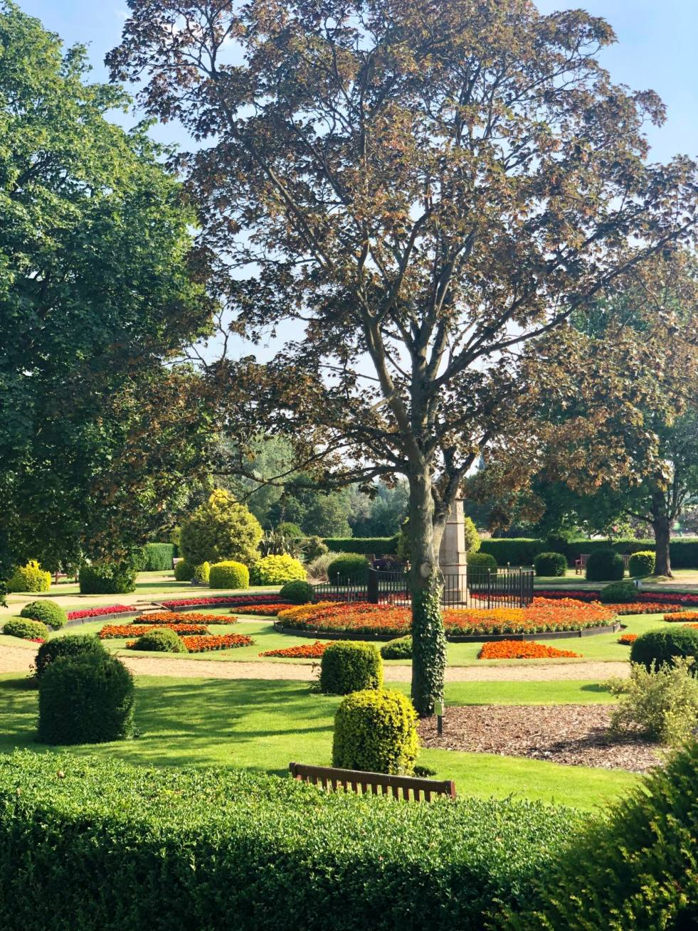 An image of green space an manicured trees in Wicksteed Park. The UK's oldest theme park, found in Kettering. A landscaped grade II listed garden with manicured borders. Fashion Voyeur Blog