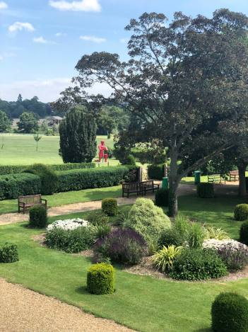 An image of green space an manicured trees in Wicksteed Park. The UK's oldest theme park, found in Kettering. The image shows a red knight seen through some trees and some shrubs. Fashion Voyeur blog
