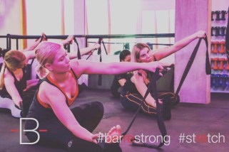 An image taken from the Barre Body Campaign shot for The Barre Workout Newcastle by Jason Holcomb featuring Pixie Tenenbaum and other clients of The Barre. This image is a close up shot of Pixie and Siobhan in an active stretch setting up for a shoulder and chest stretch