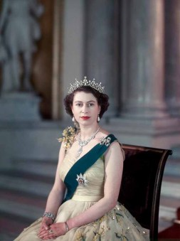 RCOD 227-X14 HM Queen Elizabeth II. Obligatory Credit - CAMERA PRESS / Baron. SPECIAL PRICE APPLIES. British monarch HM Queen Elizabeth II pictured in 1953, on the small staircase of the Grand Entrance of Buckingham Palace, wearing a yellow tulle evening gown decorated with sprays of mimosa and gold paillette. Her Majesty is also wearing the blue mantle (ribbon) of the Order of the Star of the Garter; her necklace is a wedding present from the Nizam of Hyderabad.. The priceless Cartier necklacewas a wedding present in 1947 from the Nizam of Hyderabad, a king in India.