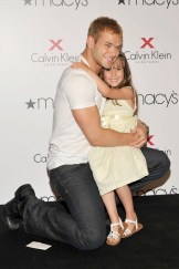 Kellan Lutz posing with a young fan