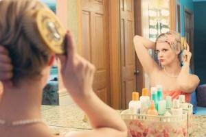 foto de una mujer peinándose delante de un espejo grande