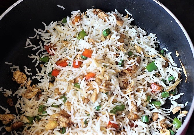 tossing chicken fried rice recipe in a black non-stick pan