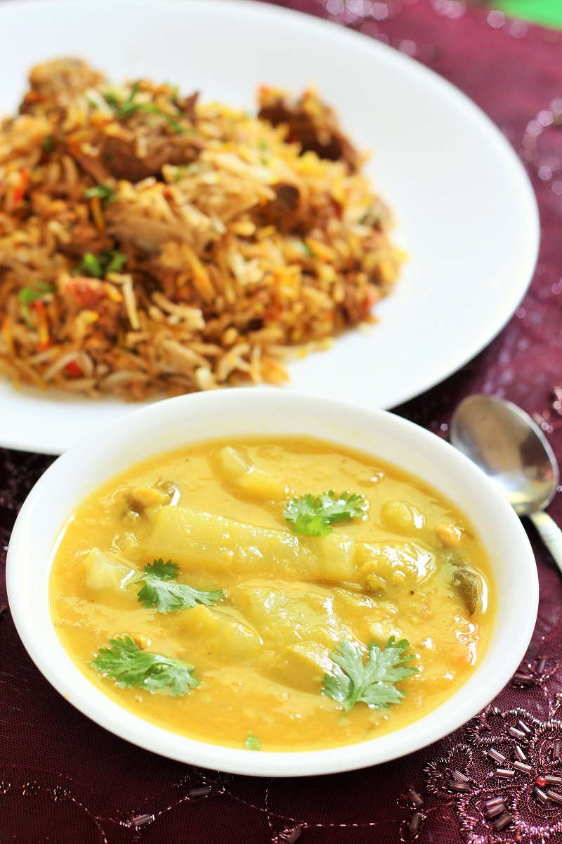 hyderabadi dalcha recipe in white bowl with biryani in the background