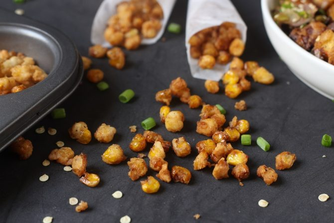crunchy corn nuts scattered on a black background
