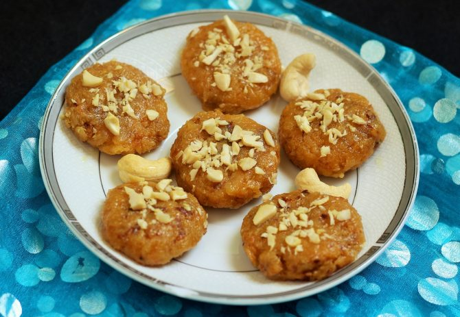 mango coconut burfi in a white plate garnished with nuts