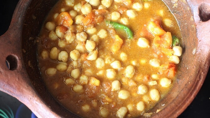 cooking chana masala recipe in a clay kadai