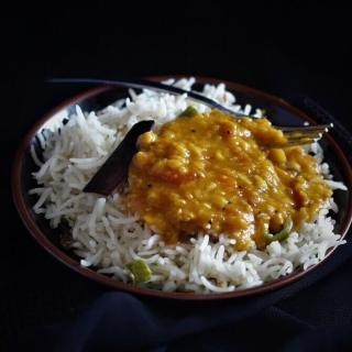 tomato dal recipe in a black plate with rice