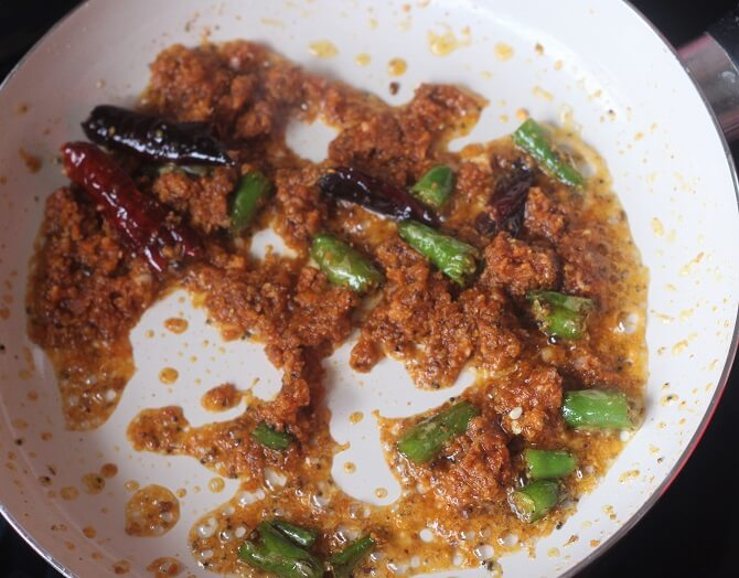 achari masala added to tadka in white pan