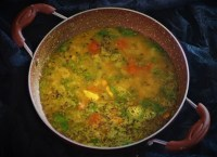 hyderabadi khatti dal recipe in a kadai with a black background