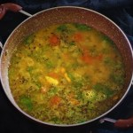 hyderabadi khatti dal recipe in a kadai with a black background