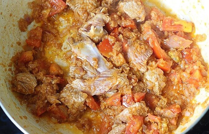 mutton added with masala in a white pan