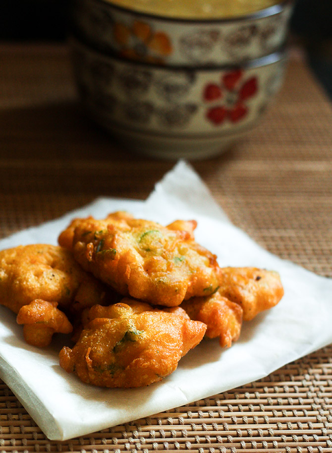 onion bhajia recipe placed on a paper towel and bowls in the background