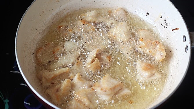 frying chicken in oil in white pan