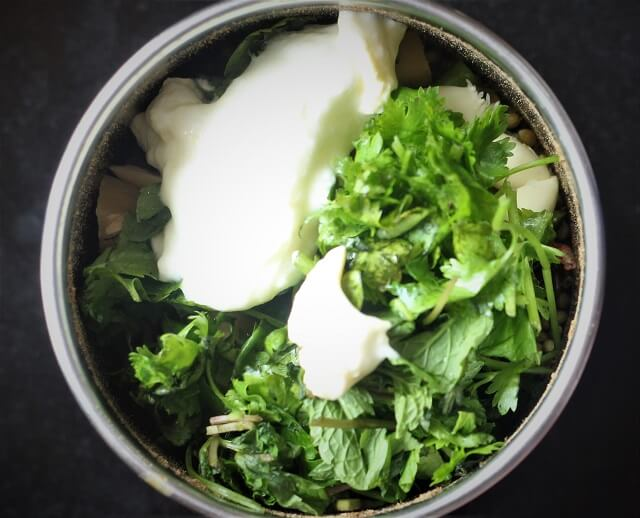 spices with coriander, mint leaves, yogurt in a mixie jar