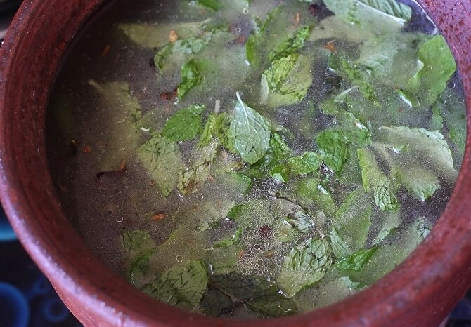 boiling water in spiced oil with mint leaves