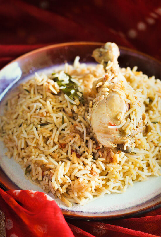 south indian chicken biryani served in a plate with chicken leg on top