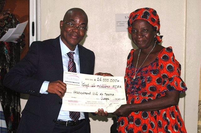 Une bénéficiaire recevant son chèque des mains du représentant de la représentante résidente de la BAD, Georges Bohoussou