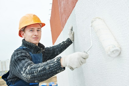 Maler streicht Hausfassade