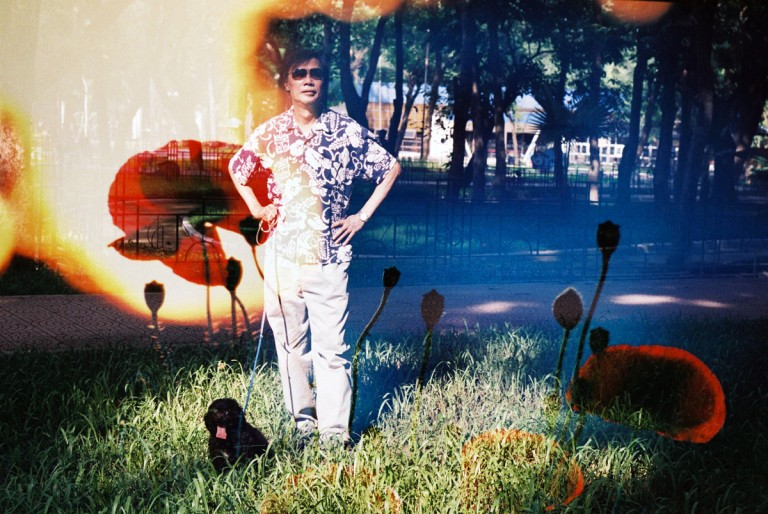 My father was standing with his dog under the sunshine in Lenin park, Hanoi, is overload by a flower from a garden in Da Lat, Viet Nam on August 2013