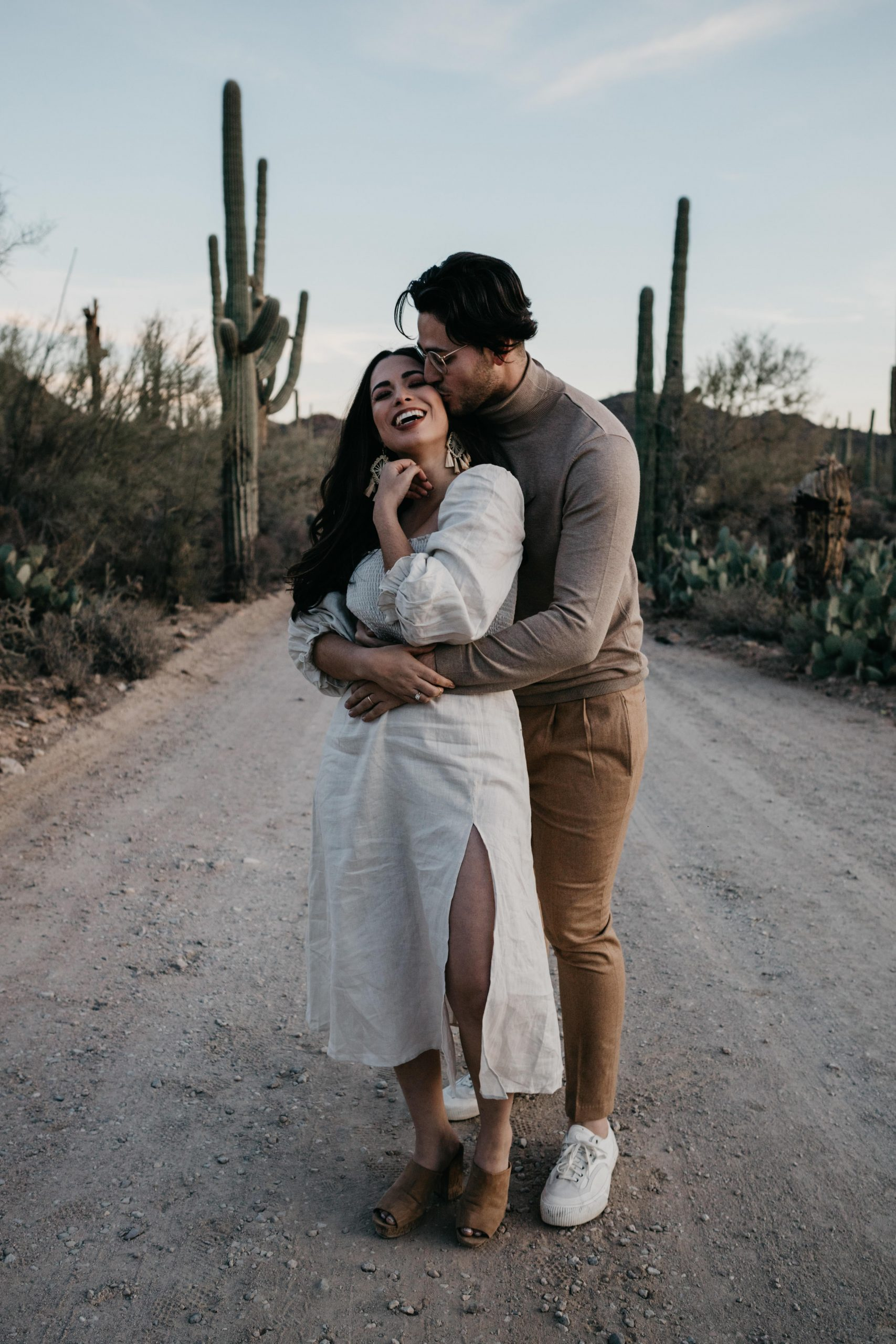 Couple embracing and laughing during desert engagement photos, image by Fatima Elreda Photo