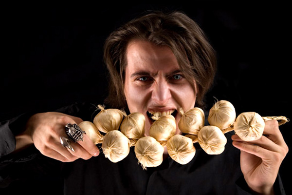 Evil vampire with scary eyes eating garlic