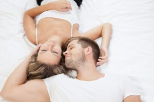 Young romantic couple lying together in bed