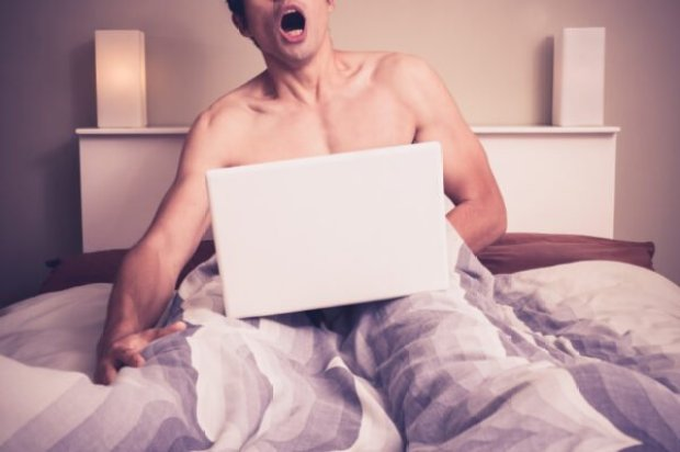 Young man is sitting in bed and watching pornography on laptop