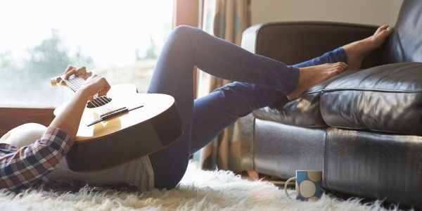 Woman at home playing guitar.