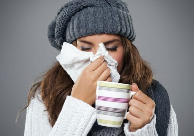 Young woman having flu and blowing her nose at handkerchief