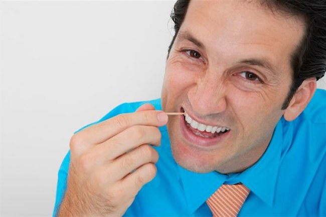678-02678267 © Masterfile Royalty Free Model Release: Yes Property Release: No Portrait of a businessman picking his teeth in an office