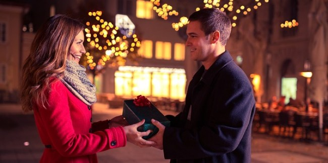 couple holding present looking at each other, young woman receives a gift from her boyfriend