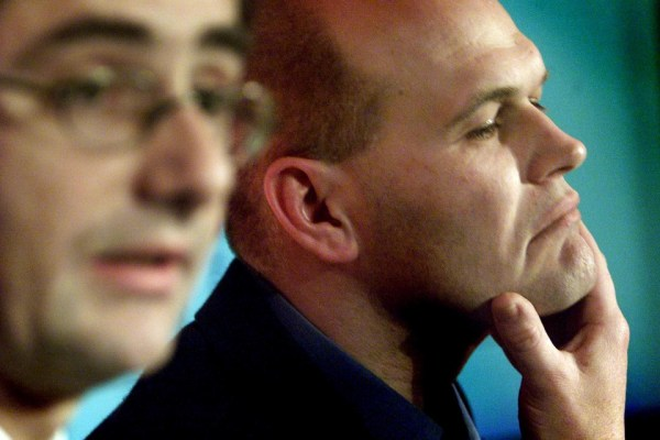 John Pluthero (R), Chief Executive Officer of British Internet service provider  'Freeserve', strokes his chin as he listens to Chairman & Chief Executive Officer of  'Wanadoo'  Nicolas Dufourcq during a news conference in Central London December 6, 2000. Shares in Freeserve and Wanadoo were suspended today pending an announcement that the biggest French and British internet companies were finalising a merger. - RTXK5U6