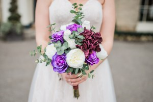 bride holding an ivory purple and claret bouquet with eucalyptus in a natural unstructured style