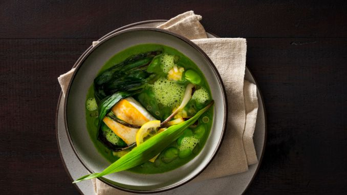 A bowl of green garlic broth with halibut, fava beans, charred ramps and finished with thinly sliced lemon, lemon relish, raw ramps and a drizzle of oil prepared by Chef/Owner Daniel Humm of NoMad