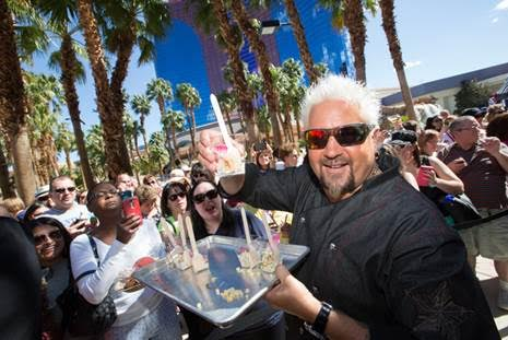 Guy Fieri hands out Corn off the Cob to a crowd outside El Burro Borracho. Credit - Erik Kabik