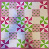 This baby quilt measures 41 inches square and is quilted in gray with hearts to wrap a baby girl in love. It is backed with the turtle print and bound with the lime green.